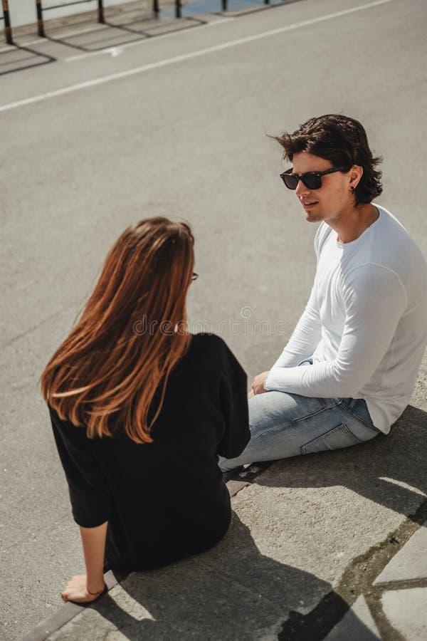 Vriend die aan zijn meisje spreken terwijl het zitten op de muur royalty-vrije stock afbeelding