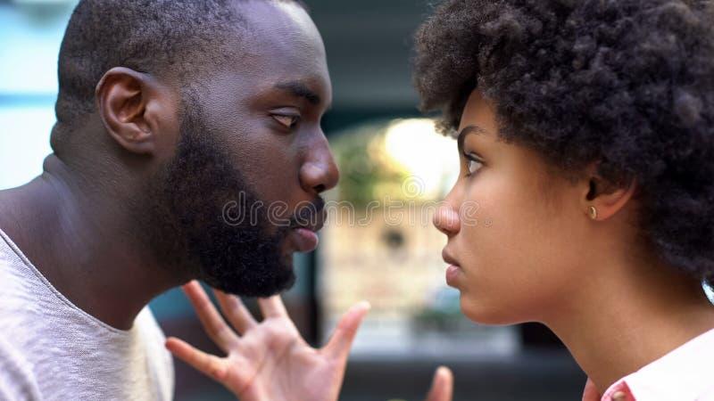 Vriend die agressief met meisje, relatiemoeilijkheden, conflict spreken stock foto's