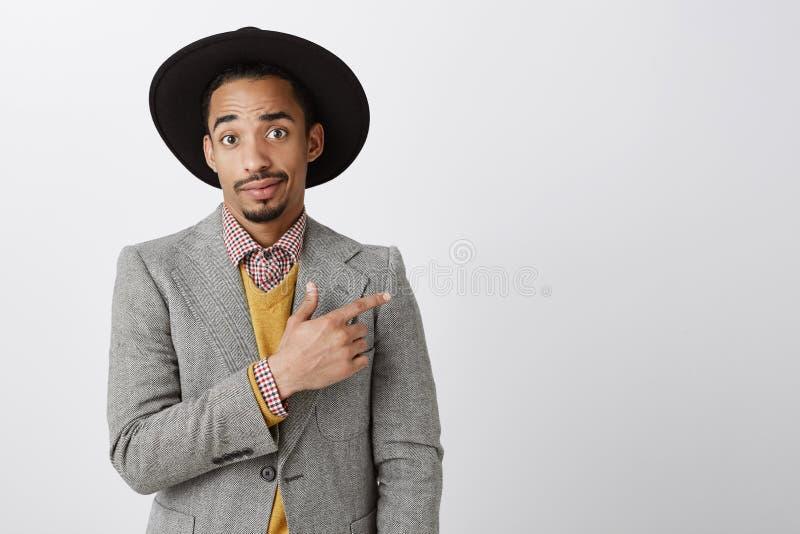 Vriend die antipathie tonen aan meisje beste vriend Ontstemde gehinderde jonge donker-gevilde kerel in zwarte hoed en royalty-vrije stock fotografie