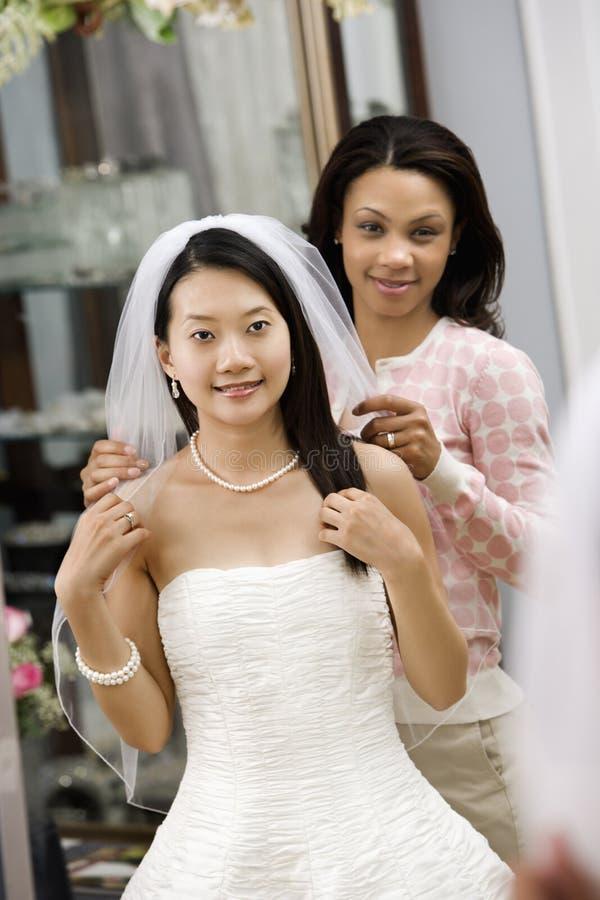 Vriend die bruid helpt. stock fotografie