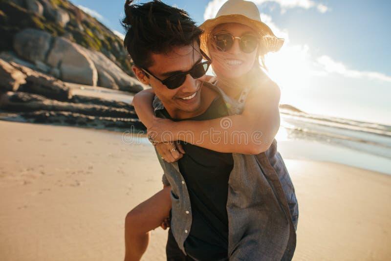 Vriend die op de rug rit geven aan meisje bij strand royalty-vrije stock fotografie