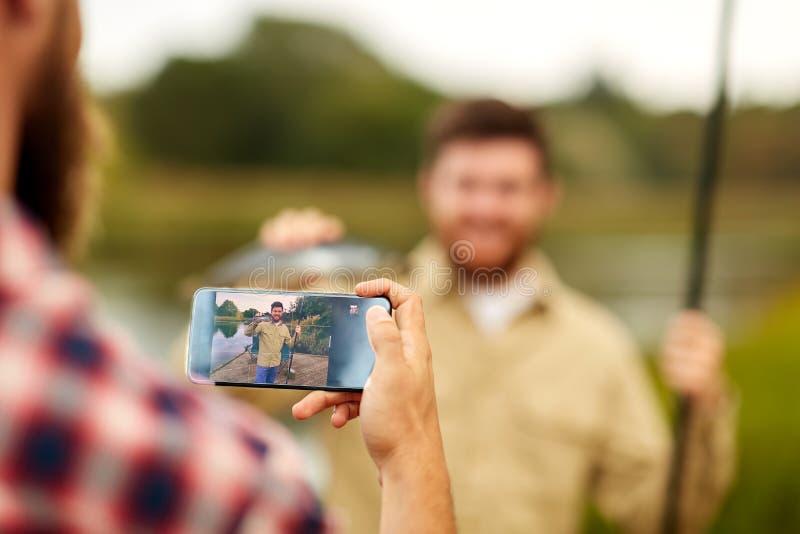 Vriend die visser fotograferen door smartphone stock afbeeldingen