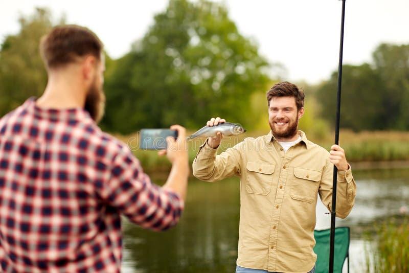 Vriend die visser met vissen fotograferen bij meer stock foto's