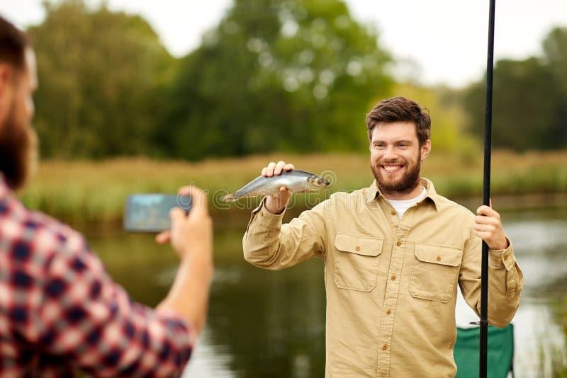 Vriend die visser met vissen fotograferen bij meer royalty-vrije stock afbeelding