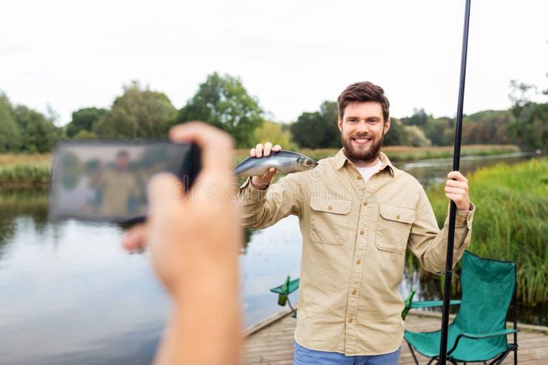 Vriend die visser met vissen fotograferen bij meer stock foto