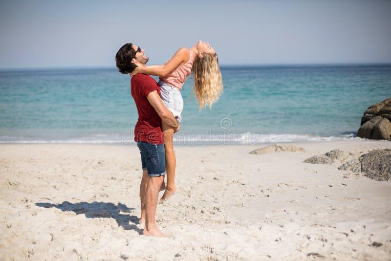 Vriend dragend meisje terwijl status bij strand royalty-vrije stock foto