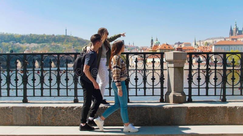 Vriend drie die op de brug lopen en rond in de Tsjech, Praag kijken stock afbeeldingen
