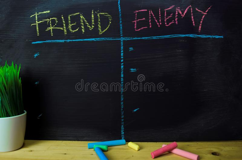 Vriend of Vijand met het concept van het kleurenkrijt op het bord wordt geschreven dat stock foto's