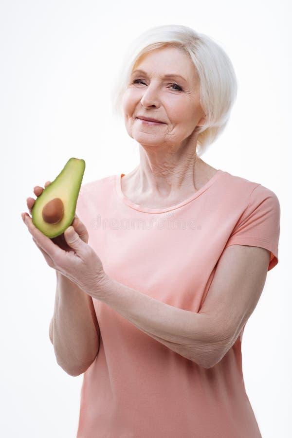 Vriendelijke het glimlachen vrouw het aantonen avocado stock fotografie