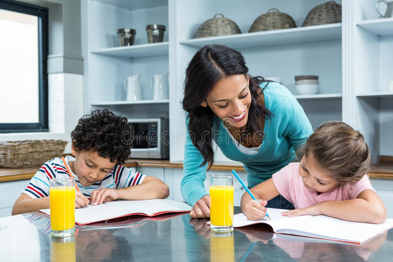 Vriendelijke moeder die haar kinderen helpen die thuiswerk doen stock foto's
