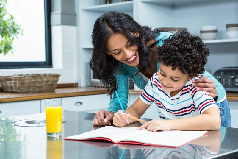Vriendelijke moeder die haar zoon helpen die thuiswerk doen stock foto's
