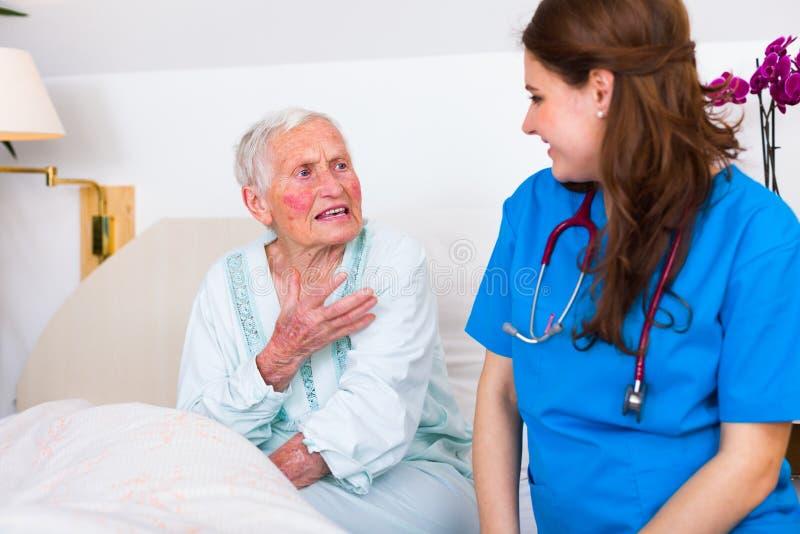 Vriendelijke verpleegster die aan hogere zieke vrouw luisteren royalty-vrije stock foto's