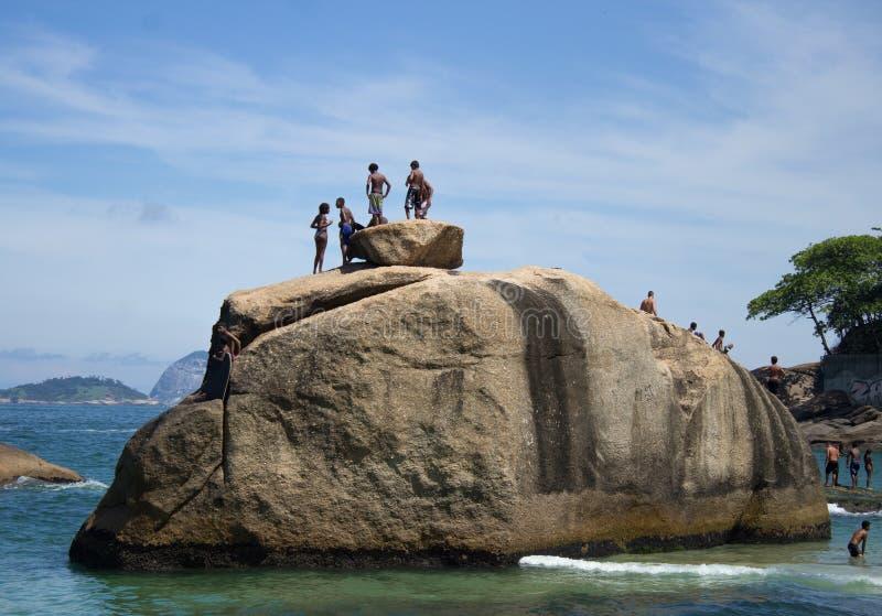 Vrienden bij de bovenkant van de rots die klaar te springen worden royalty-vrije stock fotografie