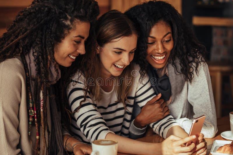 Vrienden bij een koffie die mobiele telefoon bekijken stock fotografie