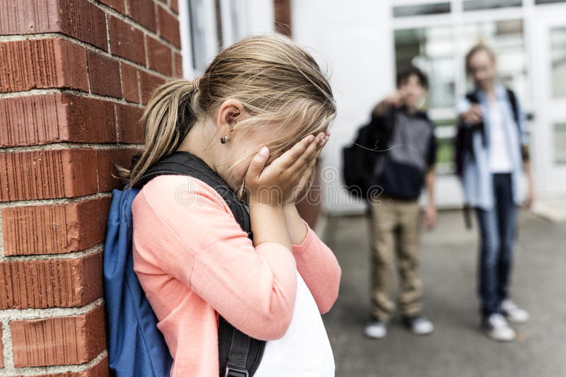 Vrienden bij een speelplaats intimidatie over ander meisje in voorgrond stock afbeeldingen