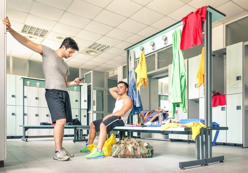 Vrienden bij gymnastiekkleedkamer - Knappe kerel bij geschiktheidsvlek stock afbeelding