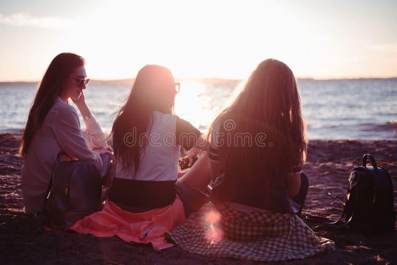 Vrienden bij zonsondergang door de oceaan schilderachtige meningen van aard Rode zonsondergang op het strand stock afbeeldingen
