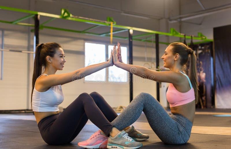 Vrienden die abs training doen en hoogte vijf geven stock afbeelding