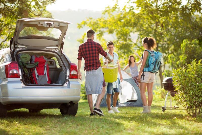 Vrienden die auto voor het kamperen uitpakken royalty-vrije stock afbeelding