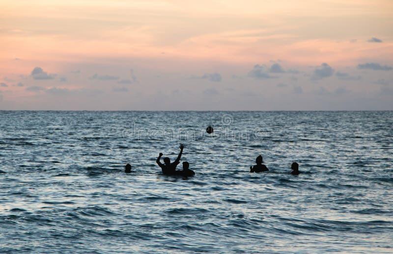 Vrienden die Bal in Oceaan spelen bij Schemer stock foto