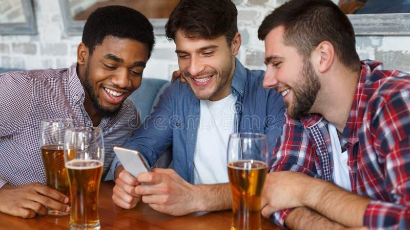 Vrienden die in bar samenkomen, smartphone gebruiken en bier drinken royalty-vrije stock afbeeldingen
