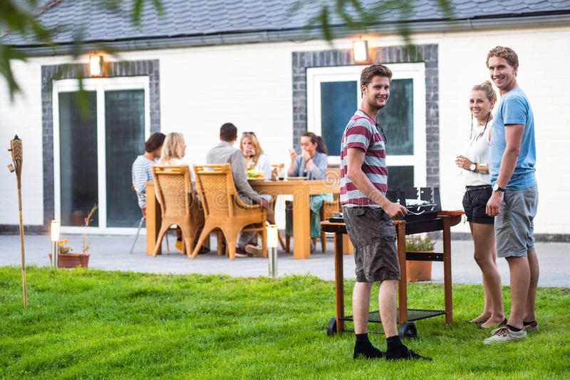 Vrienden die barbecue in achtertuin voorbereiden stock fotografie