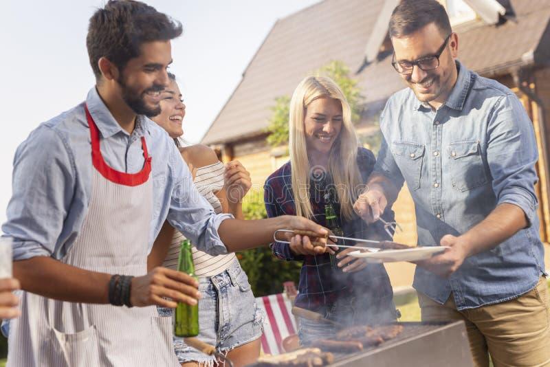 Vrienden die barbecue maken royalty-vrije stock afbeeldingen
