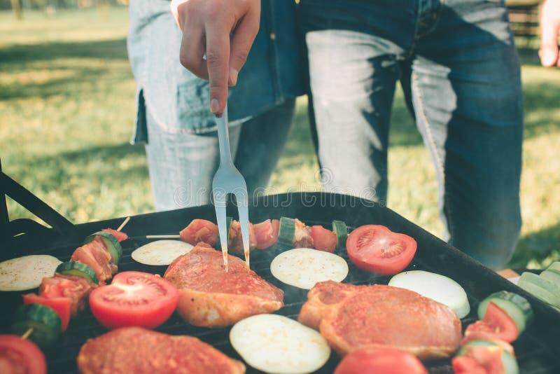 Vrienden die barbecue maken en lunch in de aard hebben Paar die pret hebben terwijl het eten en het drinken bij een Gelukkige pic royalty-vrije stock foto