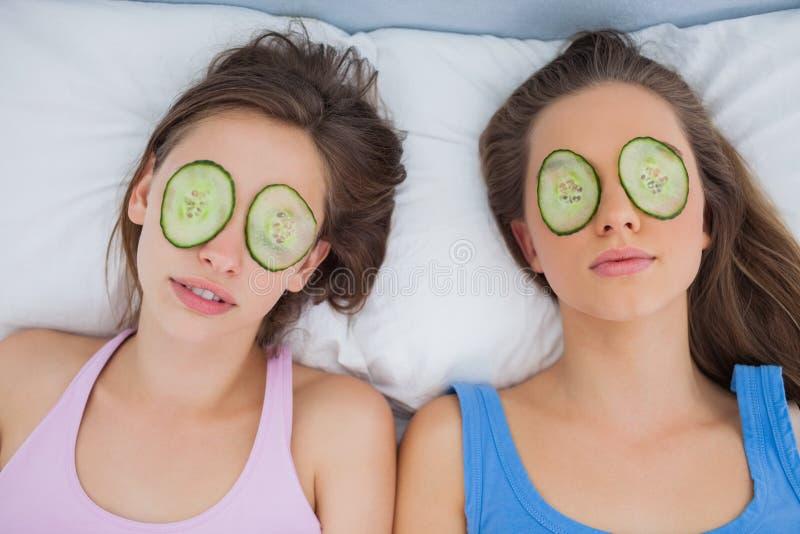 Vrienden die in bed met komkommerplakken liggen op ogen royalty-vrije stock foto