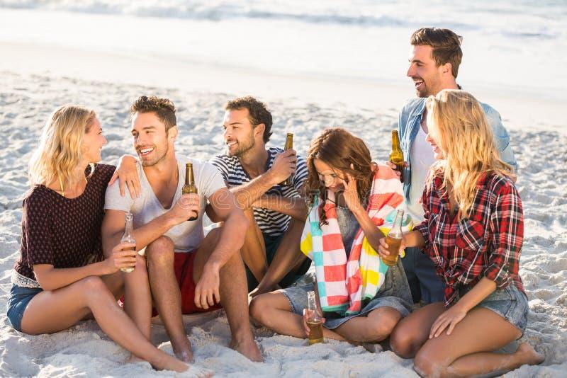 Vrienden die bier drinken bij het strand stock afbeelding