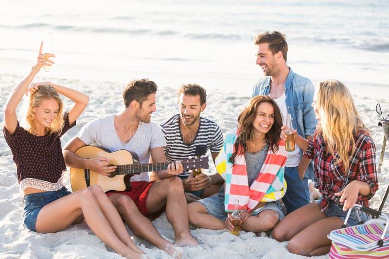Vrienden die bier drinken bij het strand stock fotografie