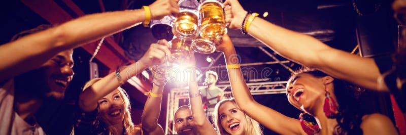 Vrienden die bierglazen roosteren bij lijst in club stock afbeeldingen