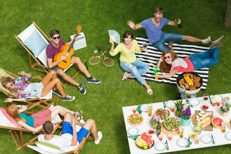 Vrienden die bij barbecuepartij ontspannen royalty-vrije stock afbeeldingen