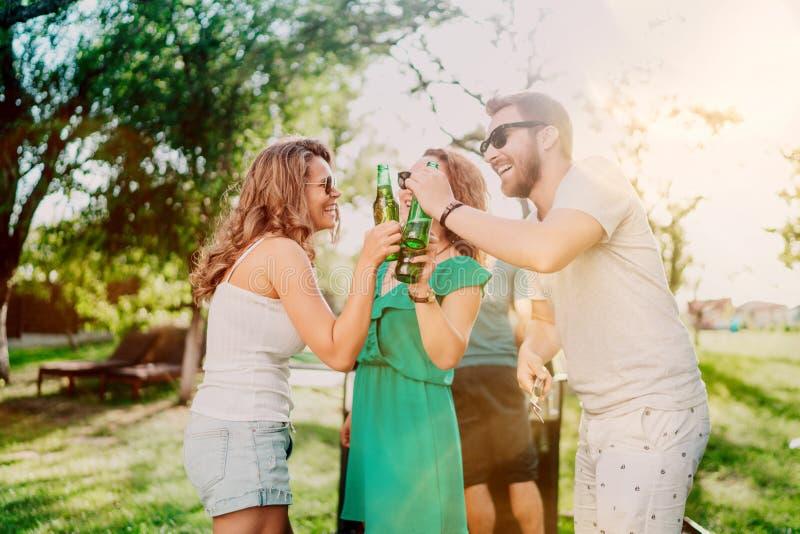 Vrienden die bij de grill tijdens zomer koken Portret van vrienden die en een partij van de tuinbarbecue roosteren hebben Lachend stock afbeeldingen