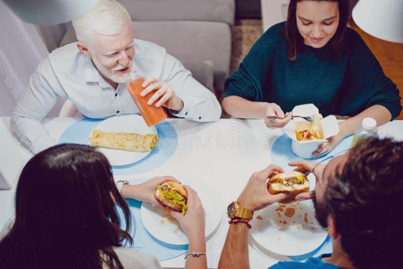 Vrienden die bij diner in het huis glimlachen stock foto's