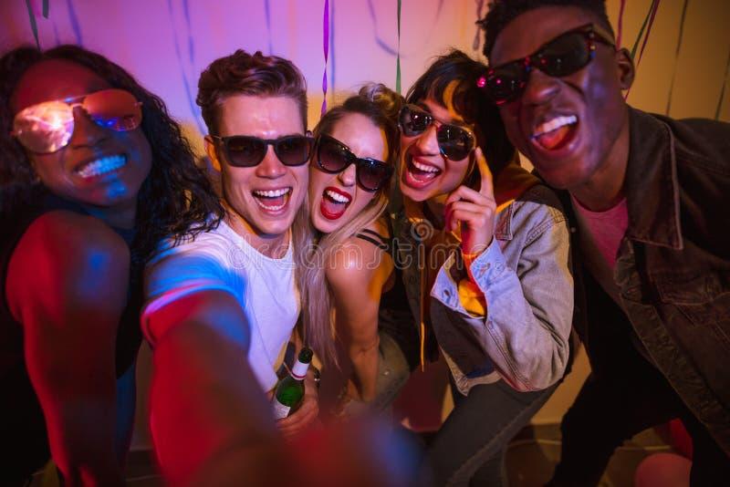 Vrienden die bij een huispartij genieten van stock foto