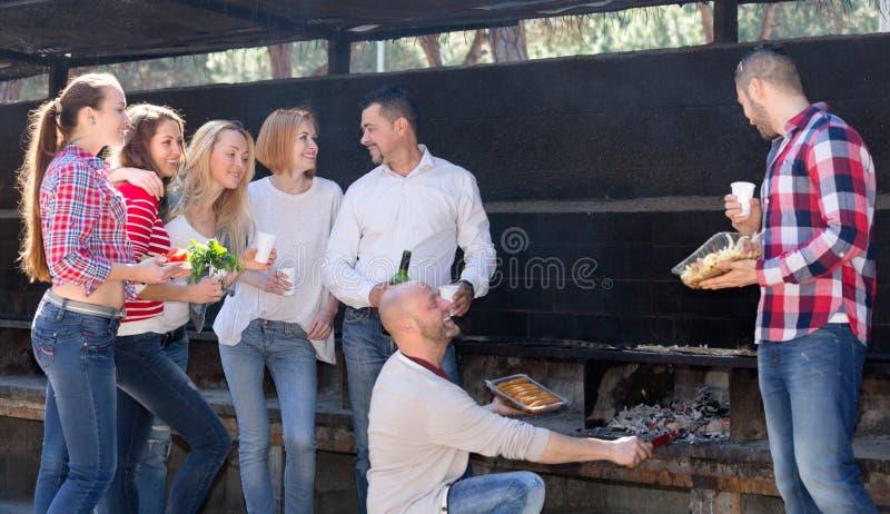 Vrienden die bij grillpartij ontspannen stock foto's