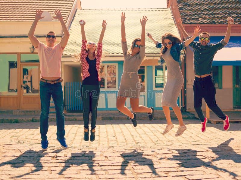 Vrienden die bij zonnige dag op de straat springen royalty-vrije stock afbeeldingen