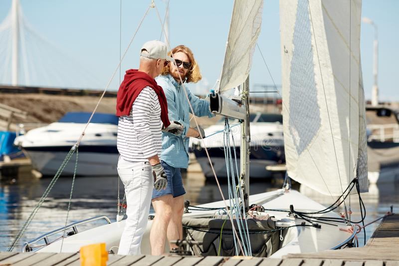 Vrienden die boot voor het varen voorbereiden royalty-vrije stock foto