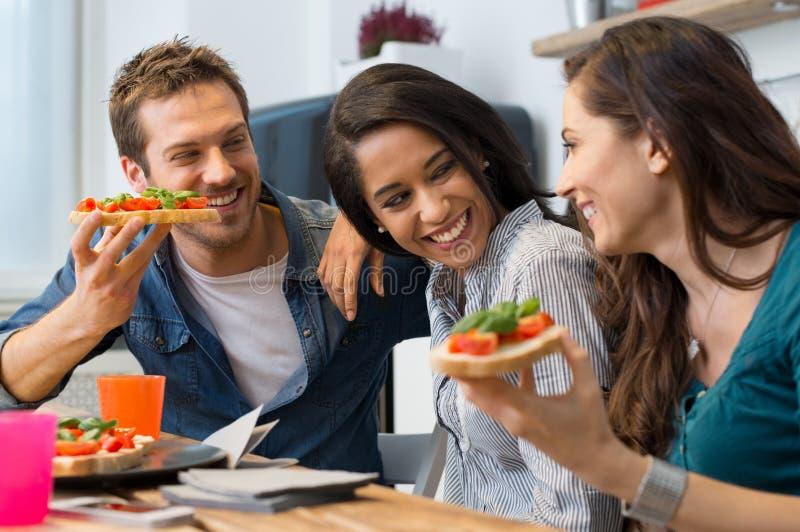 Vrienden die bruschetta eten stock foto's