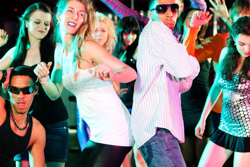 Vrienden die in club of disco dansen stock afbeeldingen
