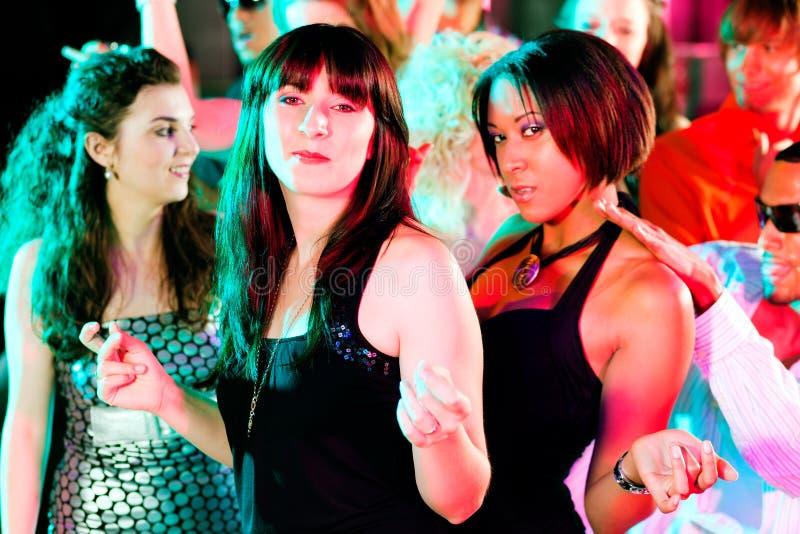 Vrienden die in club of disco dansen stock fotografie