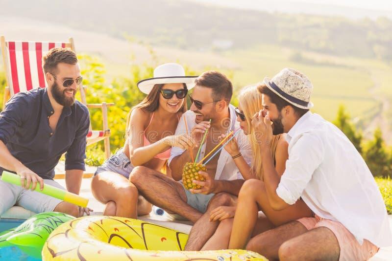 Vrienden die cocktails drinken bij een poolsidepartij stock afbeeldingen