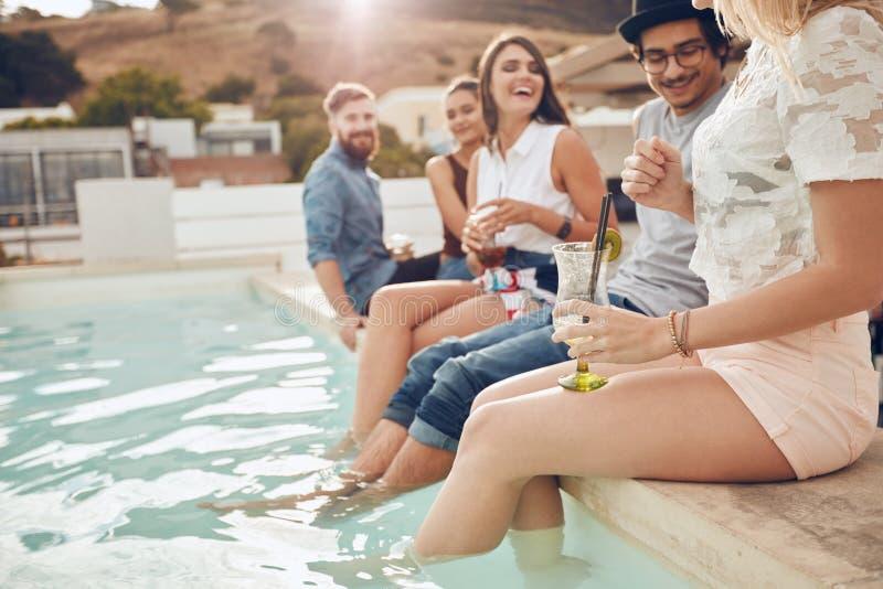 Vrienden die cocktails drinken het zwembad stock fotografie