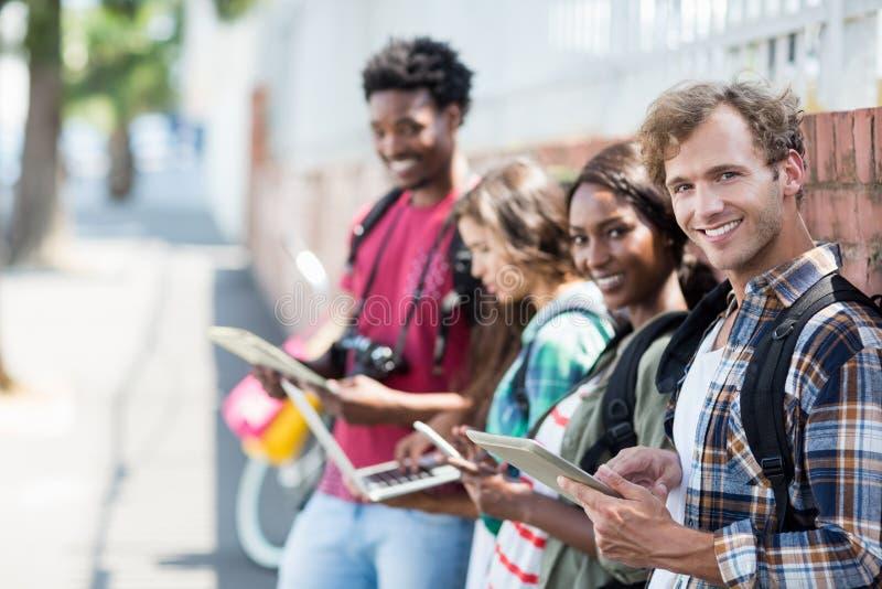 Vrienden die digitale lijst, laptop en mobiele telefoon met behulp van royalty-vrije stock foto's