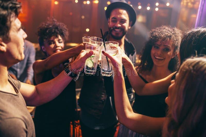 Vrienden die dranken hebben bij de partij van de nachtclub stock foto's