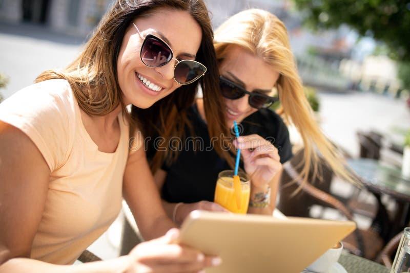 Vrienden die een grote tijd in koffie hebben En sap glimlachen drinken en vrouwen die samen van genieten stock fotografie