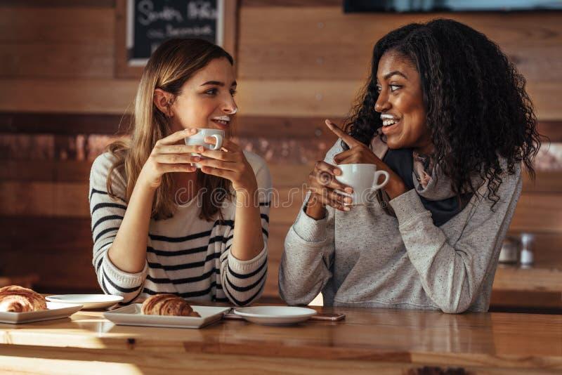 Vrienden die in een koffie het drinken koffie zitten stock foto