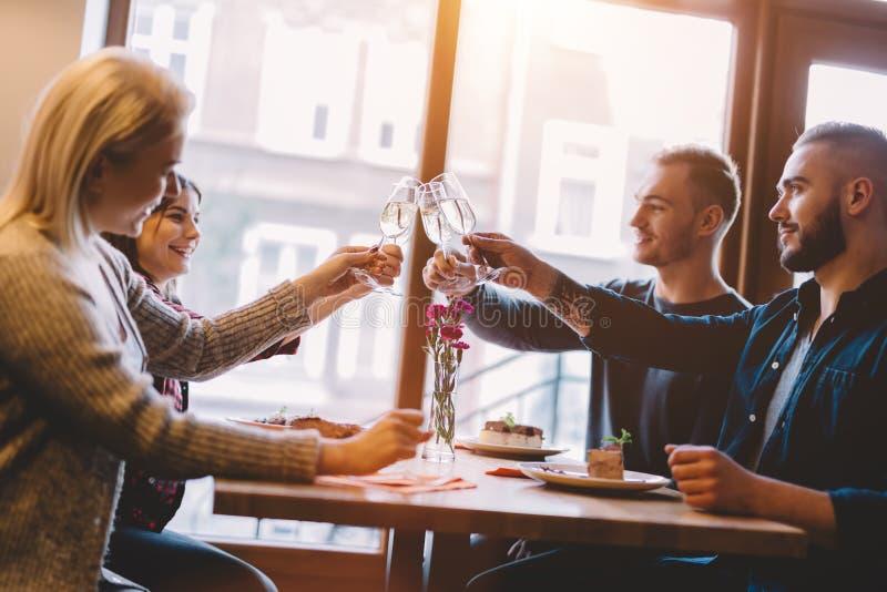 Vrienden die in een restaurant, het vieren roosteren stock afbeelding