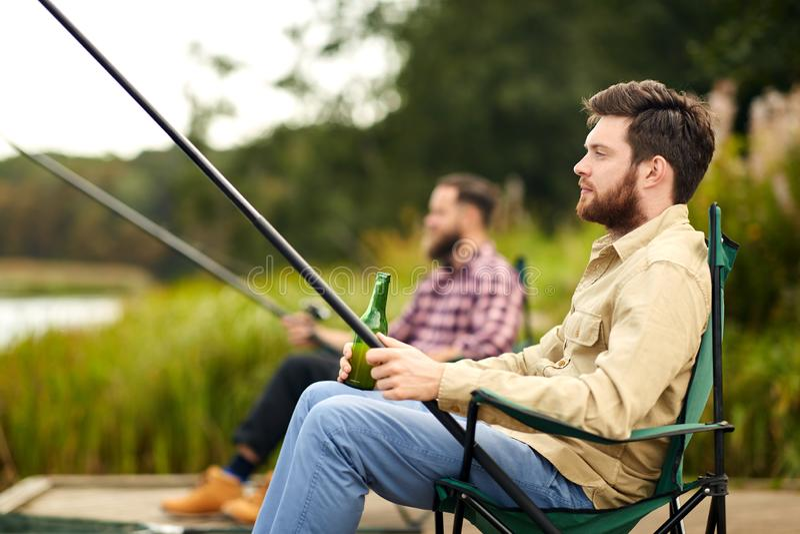 Vrienden die en bier vissen drinken bij meer royalty-vrije stock foto
